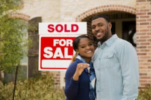 First time Home Buyer with his wife in front of their new house